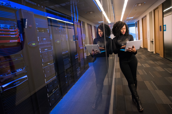 woman holding laptop glass wall