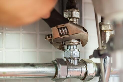 Close up of hand repairing pipes with wrench