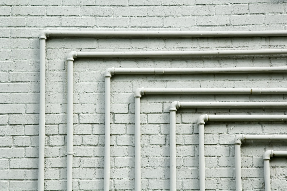 Series of parallel pipes, each with 90-degree turn, along whitewashed brick wall