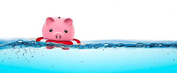 Piggy bank floating in water with life vest