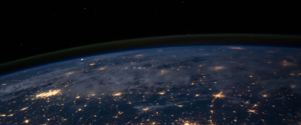 Dark aerial photo from space of Earth with lights on the globe showing connections