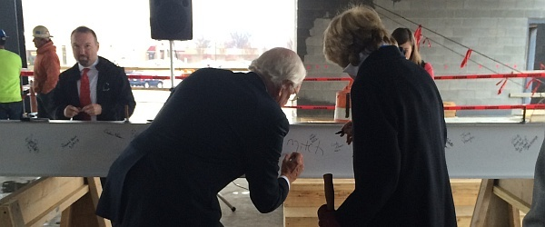 Mitch Oakley signs steel pillar to celebrate new Charles Aris building