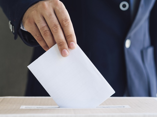 front-view-man-putting-empty-ballot-election-box_23-2148265555
