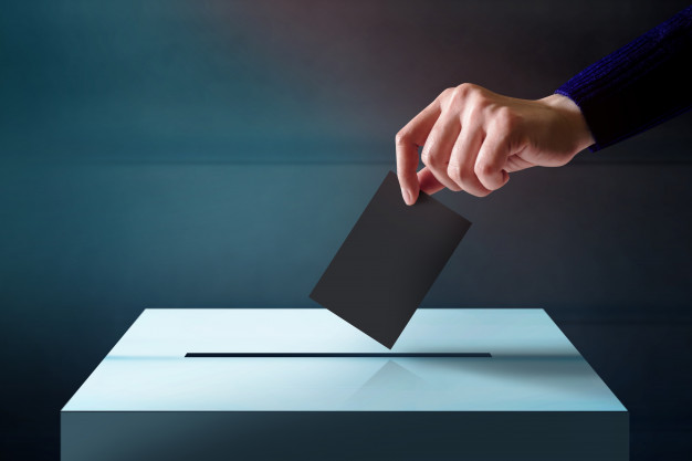 hand-dropping-a-ballot-card-into-the-vote-box_34048-85