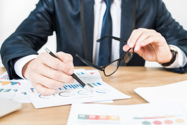 mid-section-businessman-holding-black-eyeglasses-hand-analyzing-graph-wooden-table_23-2148087127