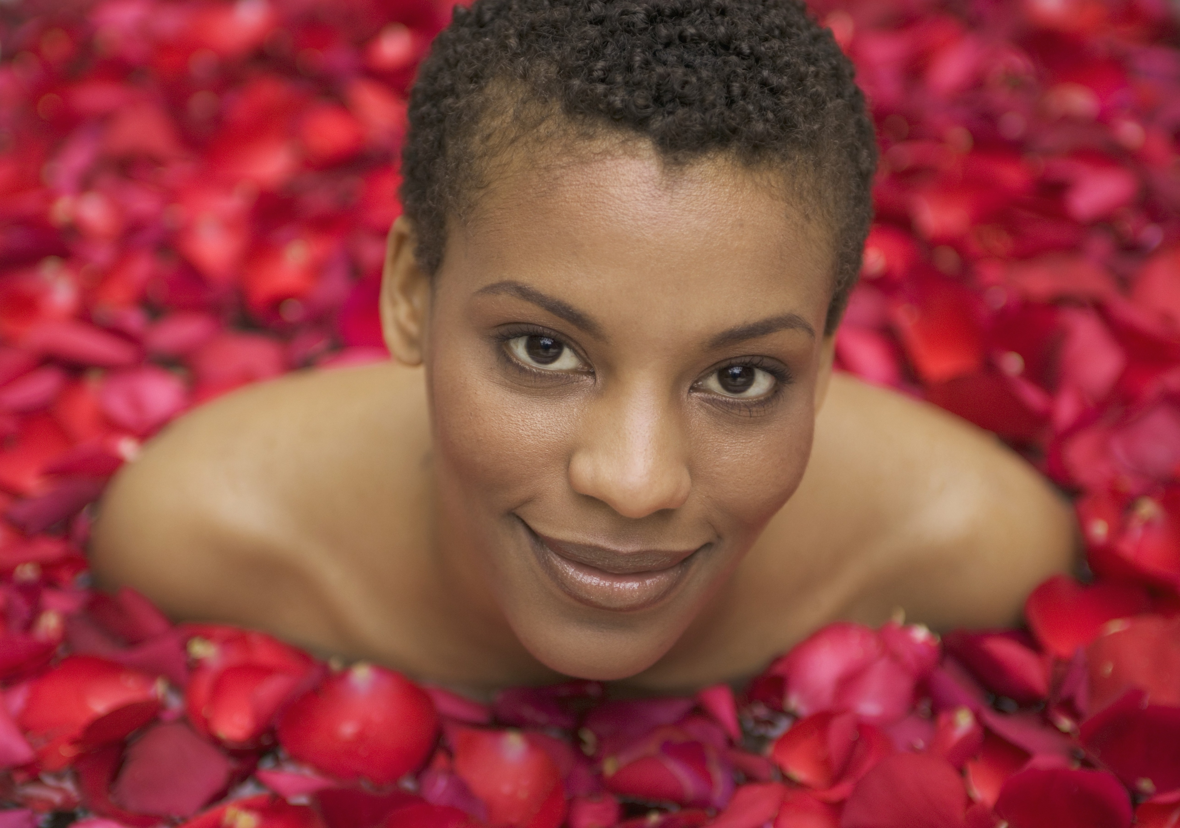 Woman smiling and surrounded by rose petals