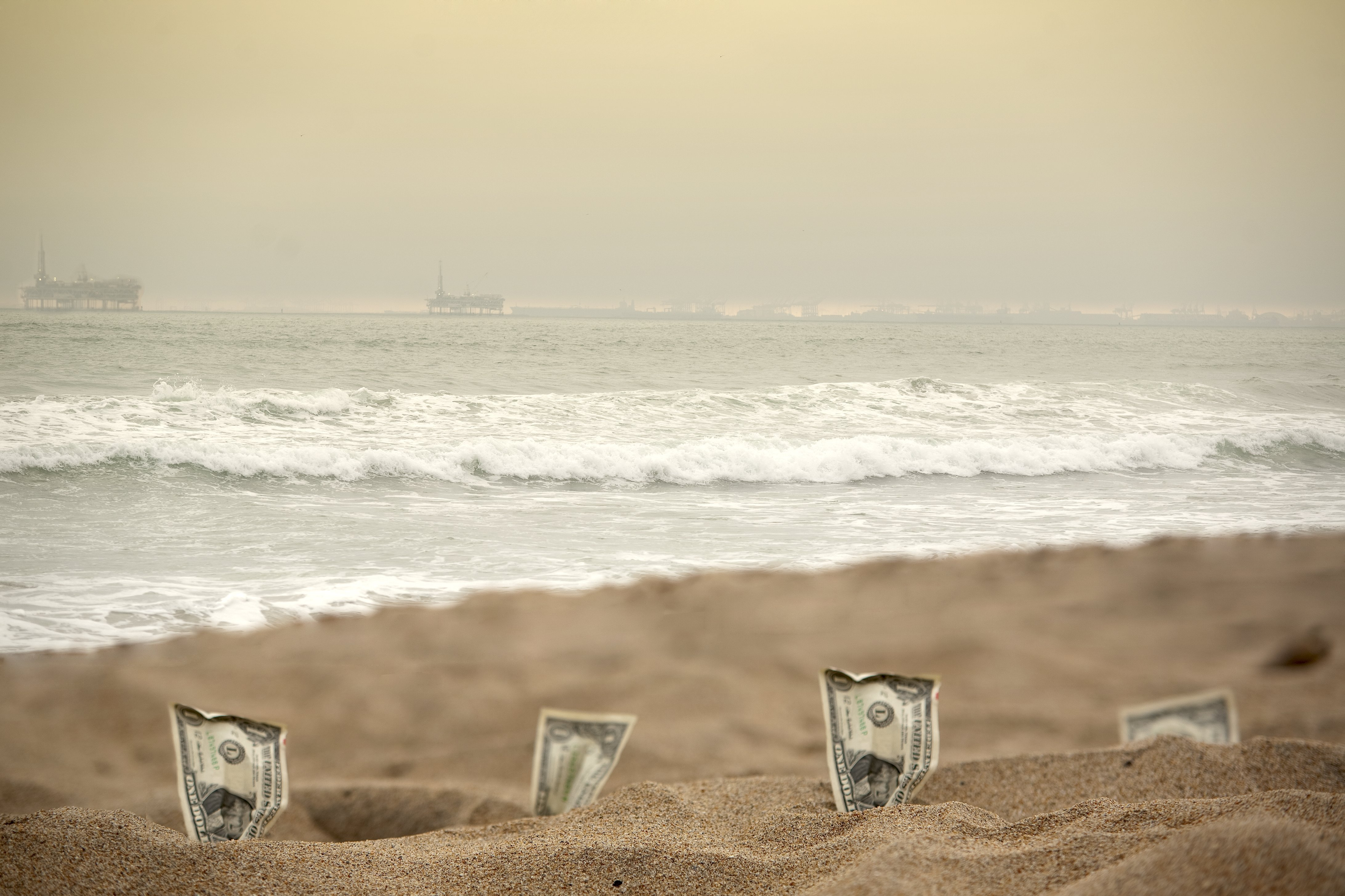 Idel cash, dollar bills laying on the beach