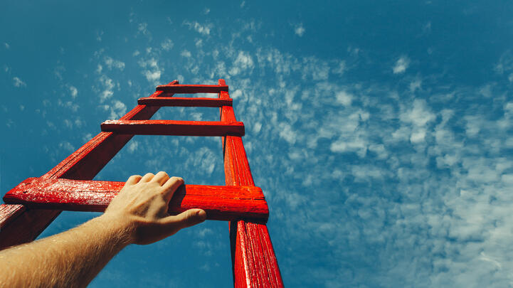 Kehitys Sergey Tinyakov by Shutterstock, ladder reaching to blue sky, hand holding them