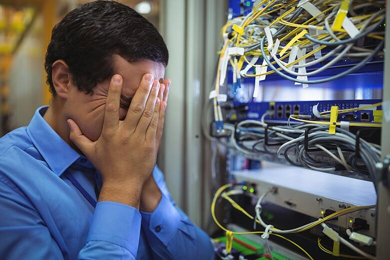 Technician getting stressed over server maintenance in server room