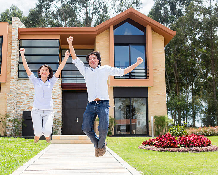 Excited couple jumping after buying a house