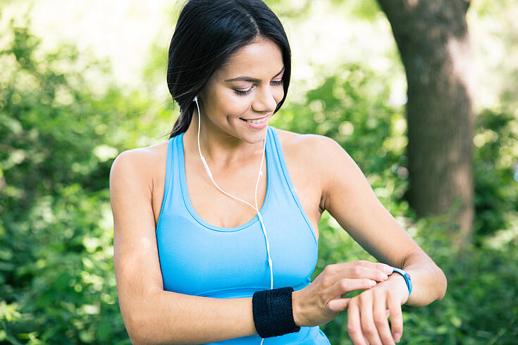 Smiling sporty woman in headphones using smart watch outdoors in park