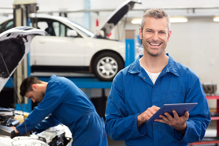 Smiling mechanic using a tablet pc at the repair garage-1