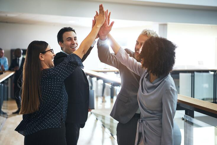cheerful-multiethnic-office-team-giving-high-five-QT8V5HN