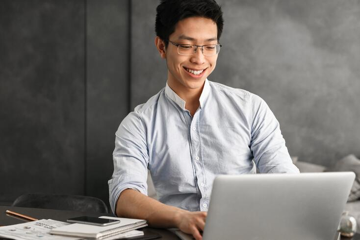 happy-young-asian-man-using-laptop-computer-NLV528T-1