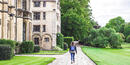 A young student walks on campus as she considers her college admissions options.