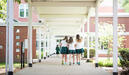 Three middle school students at The Ellis School walk together outside between classes.