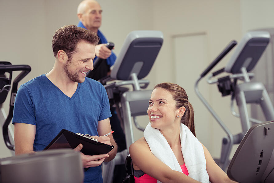 Attractive young woman with a trainer at the gym smiling up at him as they discuss her progress in a health and fitness concept
