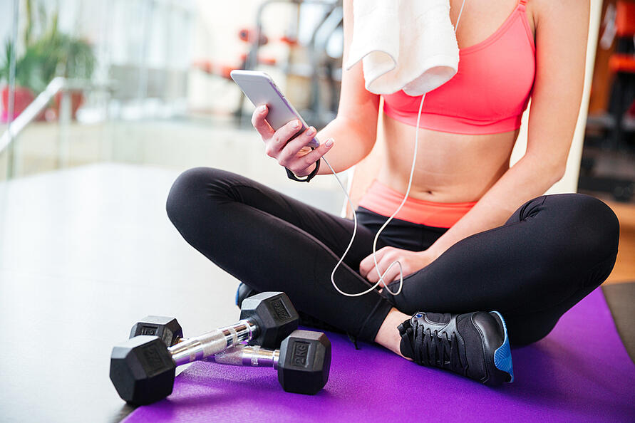 Closeup of young woman athlete sitting on mat and using mobile phone in gym