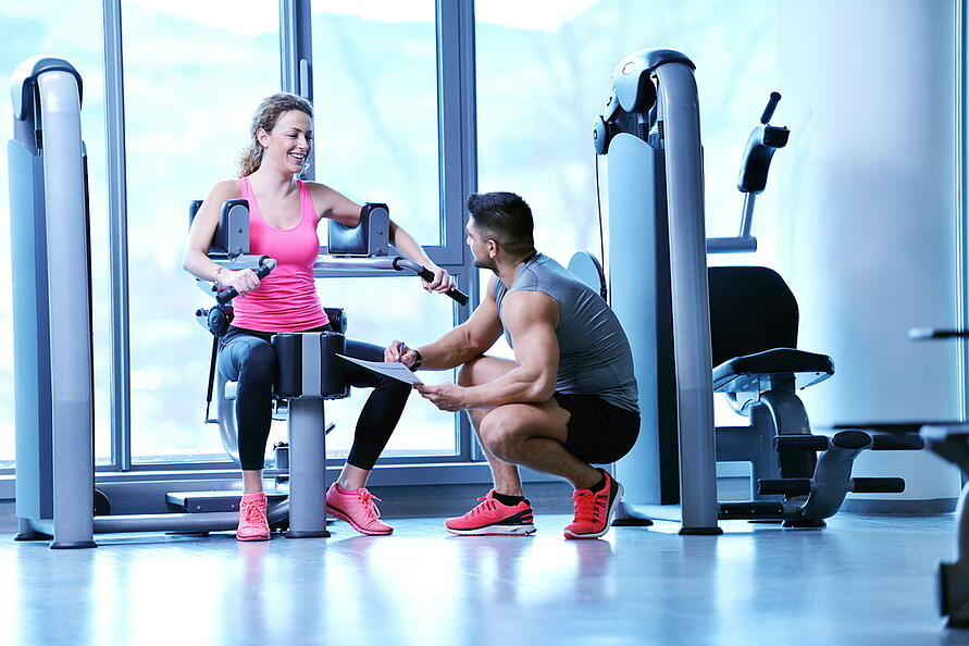 Gym woman exercising with her personal trainer-3