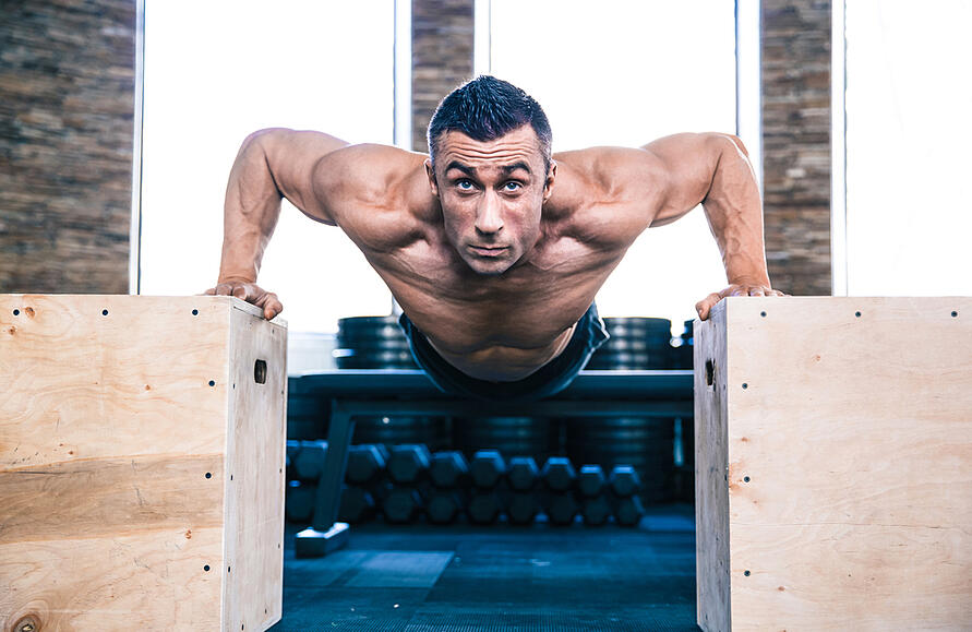 Handsome muscular man doing push ups on fit box at gym