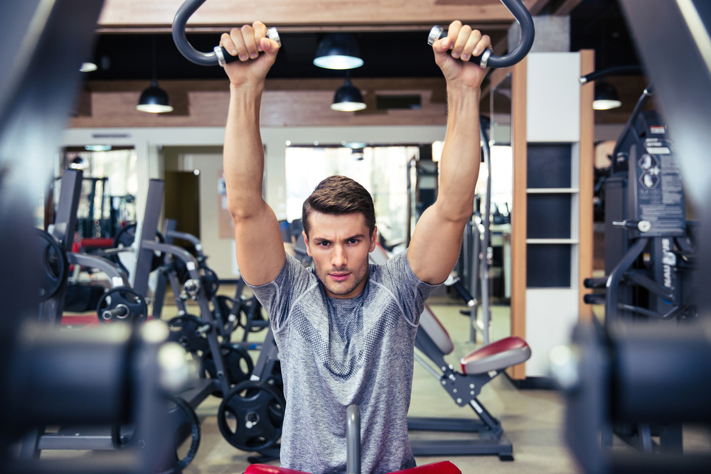 Portrait of a handsome bodybuilder doing exercise on a fitness machine in gym