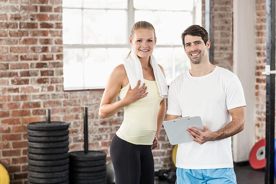 Sporty woman watching her results on clipboard in crossfit gym