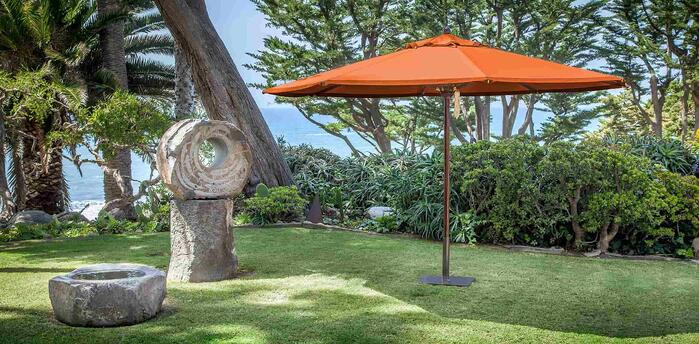 Orange umbrella in tropical setting