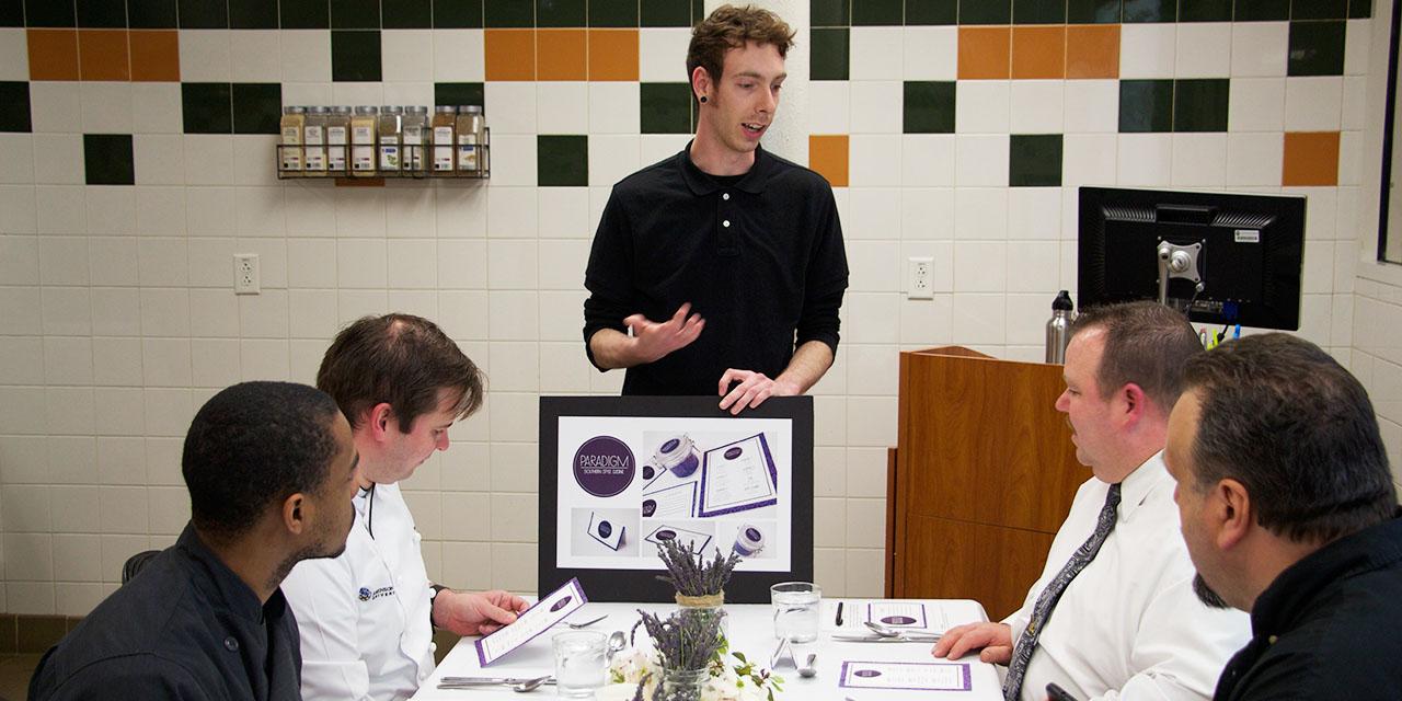 Graphic Design & Digital Media student explaining the concept behind pop-up restaurant Paradigm