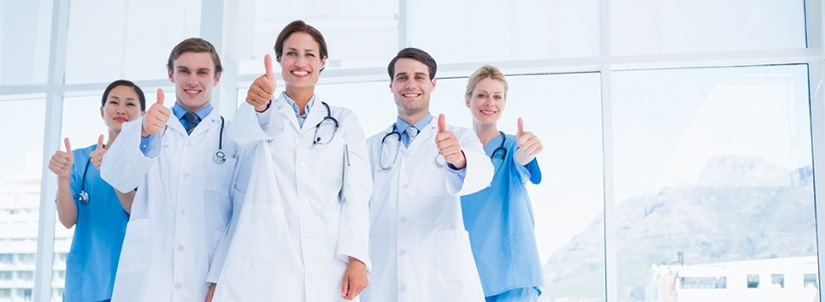 Group portrait of young doctors gesturing thumbs up at hospital