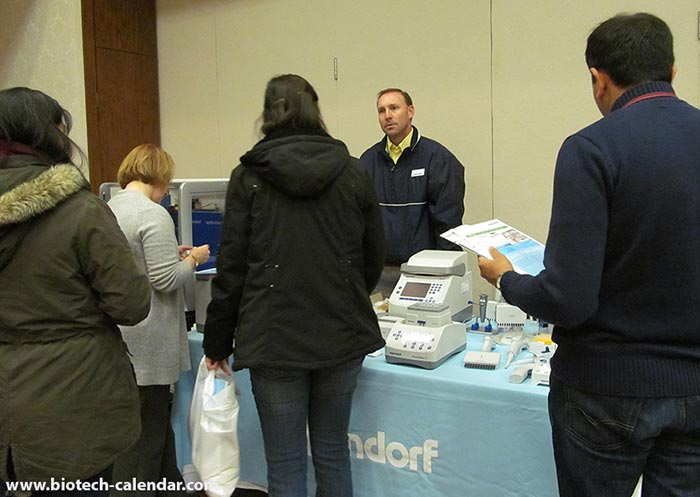 Groups of researchers check out Eppendorf's display of life science research equipment.