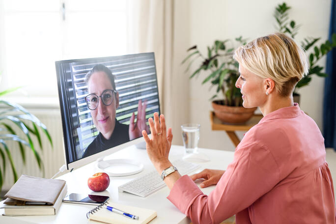 woman at desk waving to a woman on screen in a Zoom meeting during remote work
