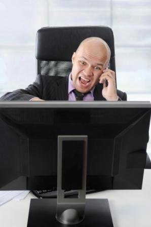 why call centers need to put people on hold - angry man at computer