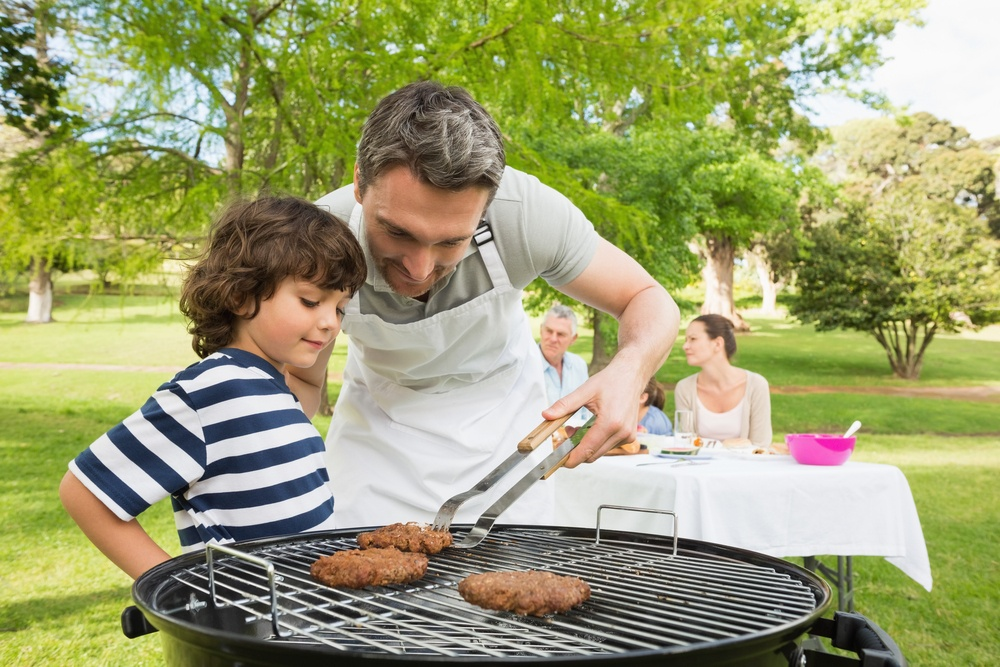 Man and son barbecuing with family in the background at park.jpeg