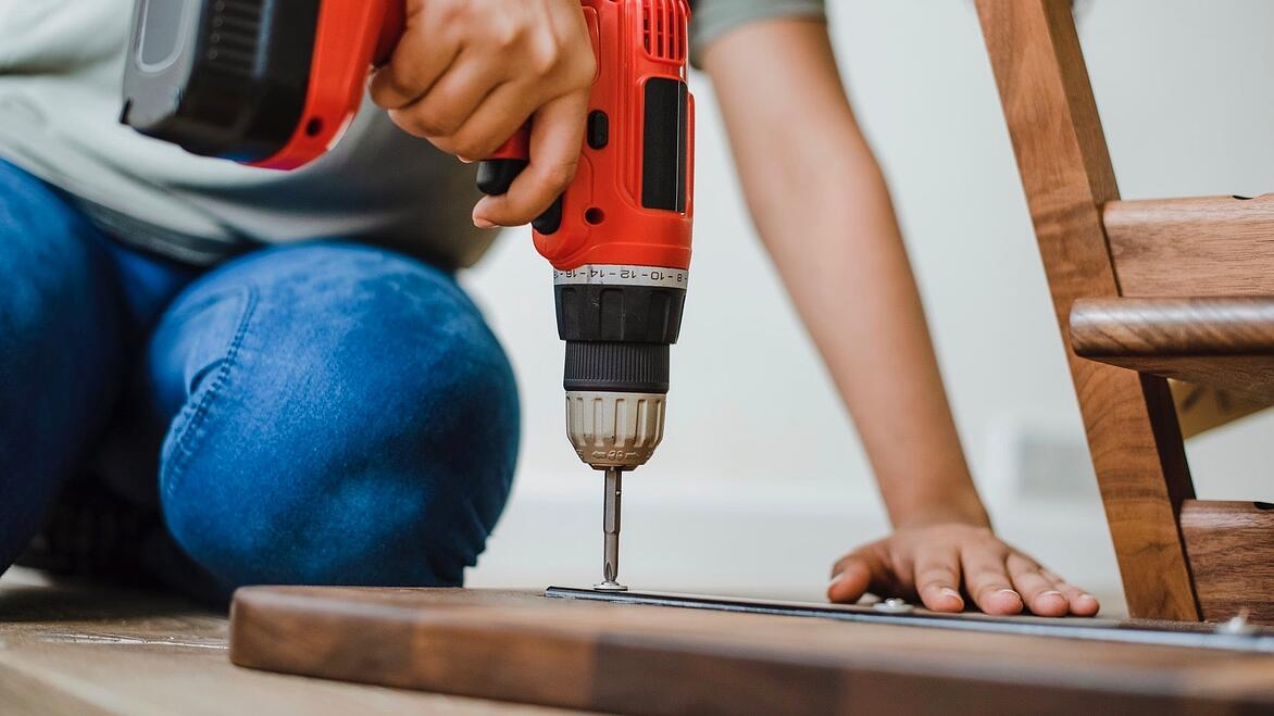 using a drill on a wooden board