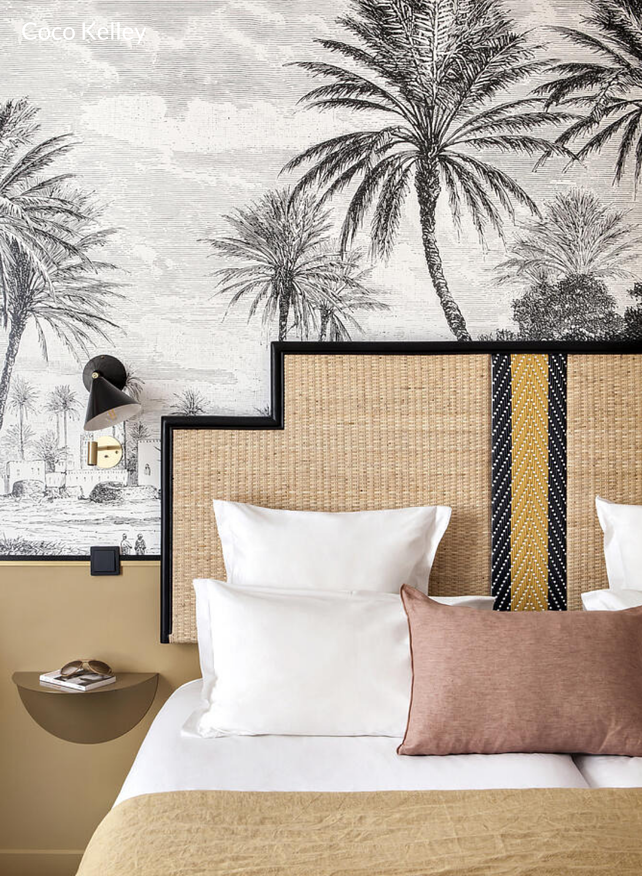 wall mural master bedroom with statement cane rattan headboard and wall lighting