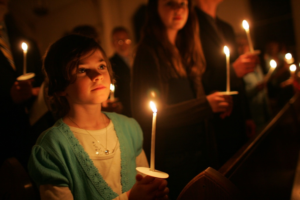 A young girl holds a candle during the Easter Vigil as part of Holy Week. Image: Flikr