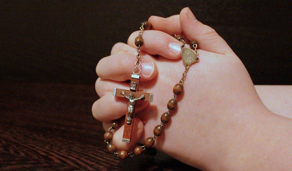 Hands clasped in prayer with a rosary wrapped around them, image via pixabay