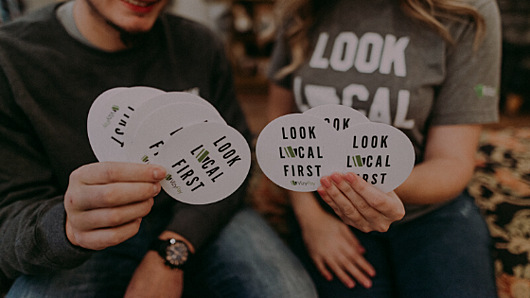 people-holding-look-local-first-stickers
