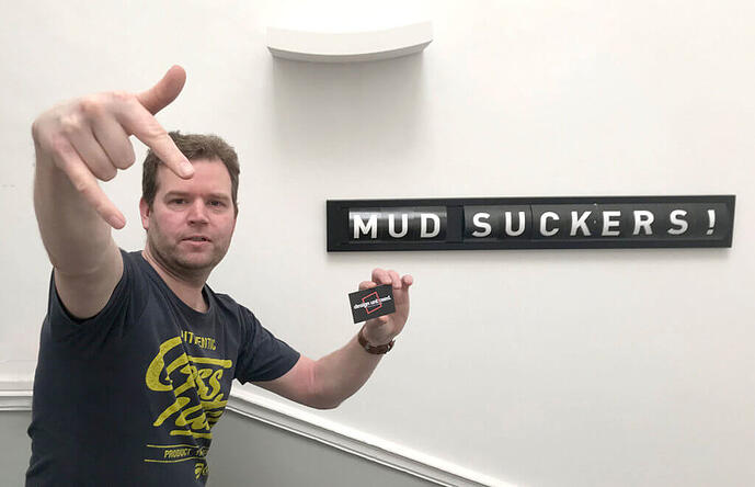 """Steven doing a gansta stance beside a sign which reads """"mud suckers!"""""""