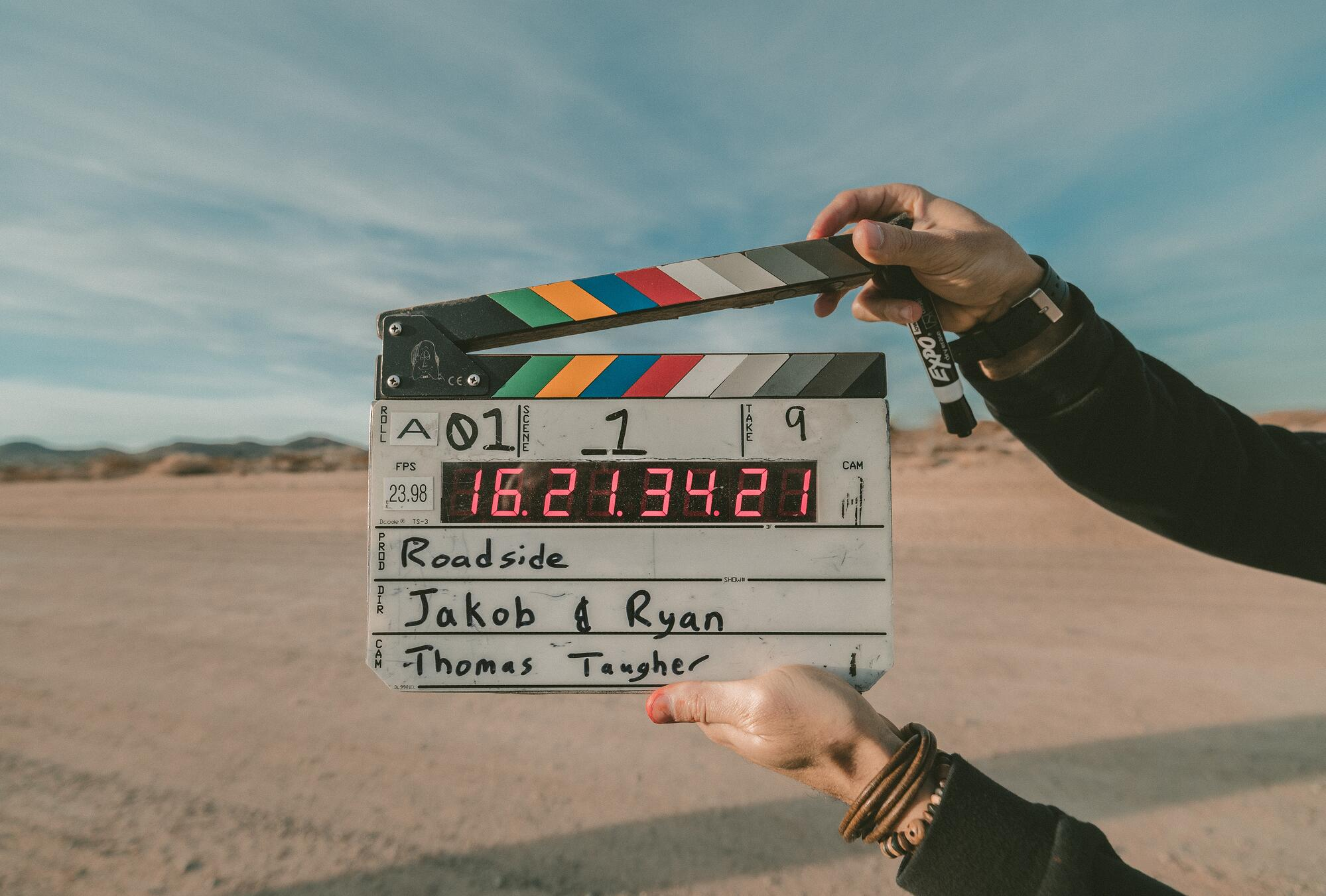 Person uses clapper board to film live action explainer video