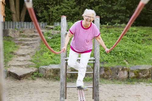 cheerful--senior-woman-on-playground-balancing-589428610_5760x3840