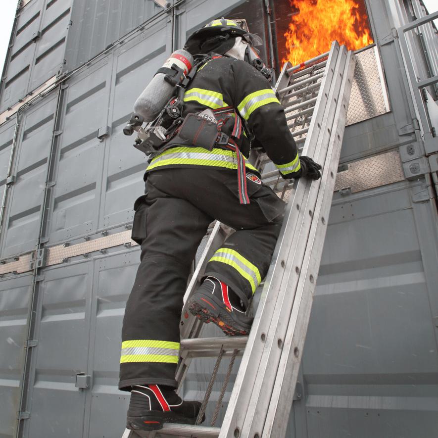 Firefighter climbing a ladder to a fire.