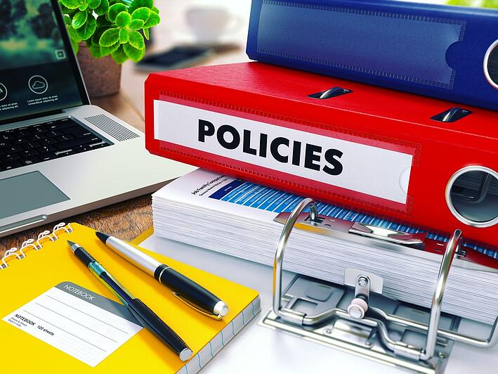 Policies - Red Ring Binder on Office Desktop with Office Supplies and Modern Laptop. Business Concept on Blurred Background. Toned Illustration.