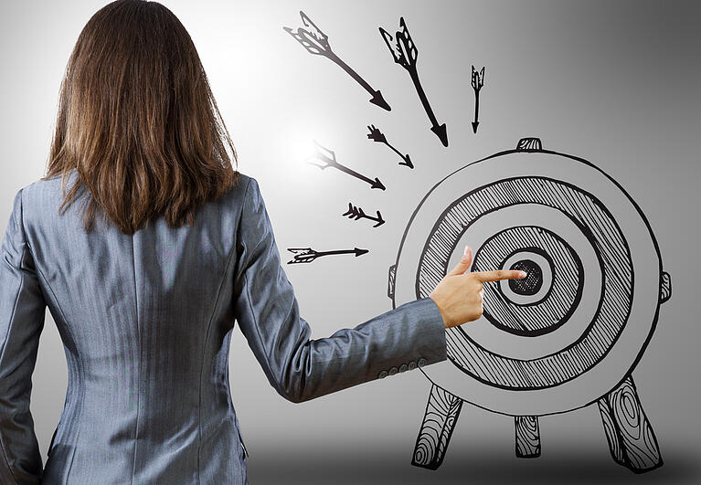 Rear view of businesswoman pointing at drawn target-1