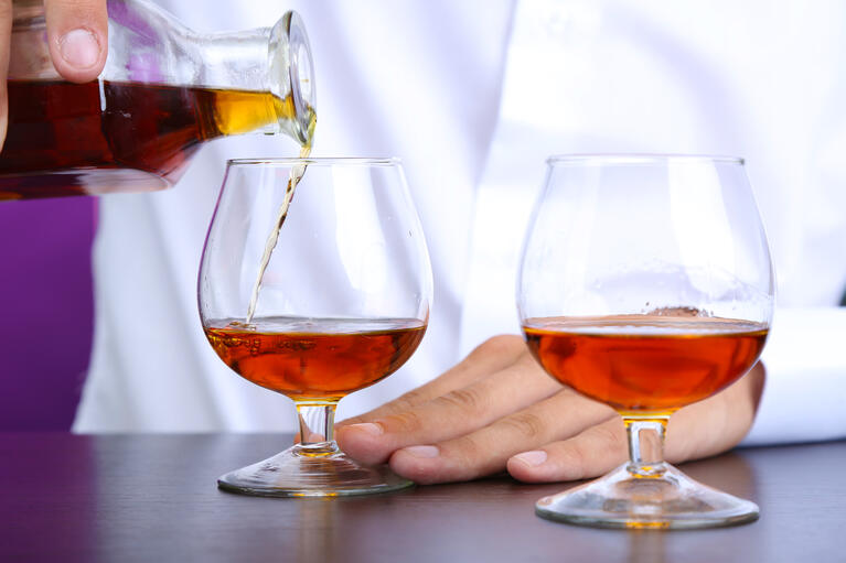 bigstock-Bartender-is-pouring-cognac-in-49977590