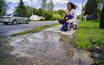 Caryn Luna holds her son Joey Farone IV, three years old, outside their home near the site of a service line break on Tuesday, June 11, 2019, in Niskayuna, N.Y. The break was discovered back on May 10th.
