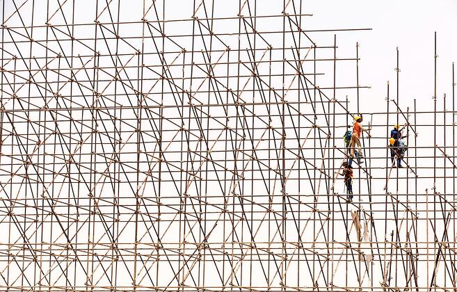Workers assemble scaffolding