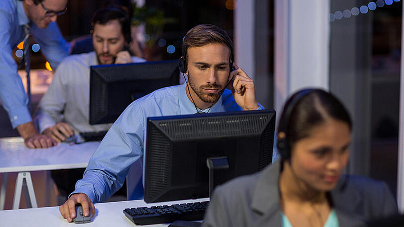 Businessman with headsets using computer in office at night
