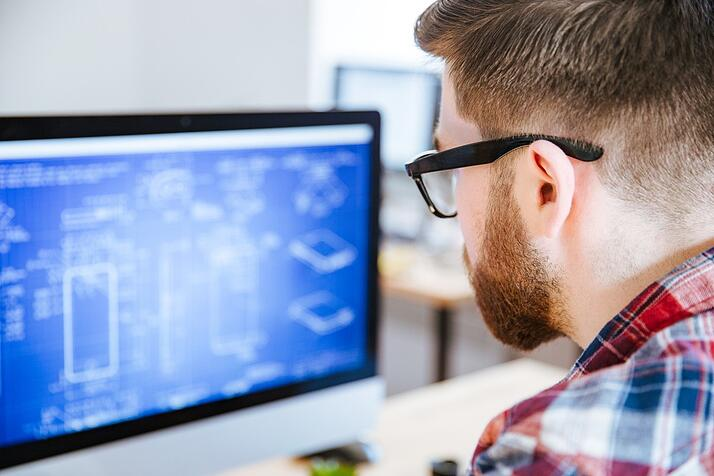 Closeup of young man in glasses with beard making blueprints on computer
