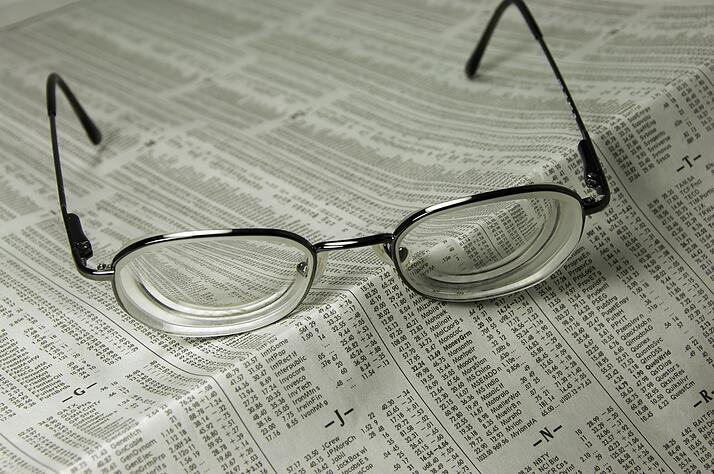 Pair of eyeglasses on financial page of daily newspaper